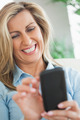 Happy blonde woman typing on her mobile phone - PhotoDune Item for Sale