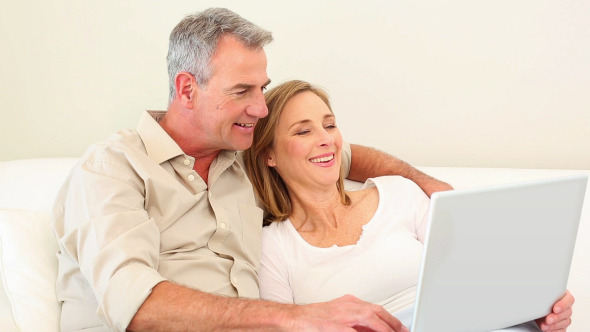 Mature Couple Using Laptop Together On The Couch