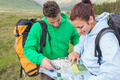 Couple sitting after hiking uphill and consulting map in the countryside