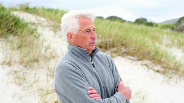 Retired Man Standing On The Beach Shivering