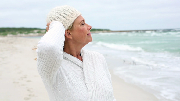 Retired Woman Standing On The Beach Looking Out