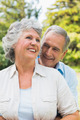 Smiling mature couple together in park embracing and laughing