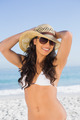 Happy attractive brunette with straw hat and sunglasses on the beach