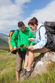 Attractive couple resting after hiking uphill and consulting map and compass in countryside