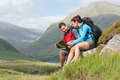 Couple taking a break after hiking uphill and reading map in the countryside
