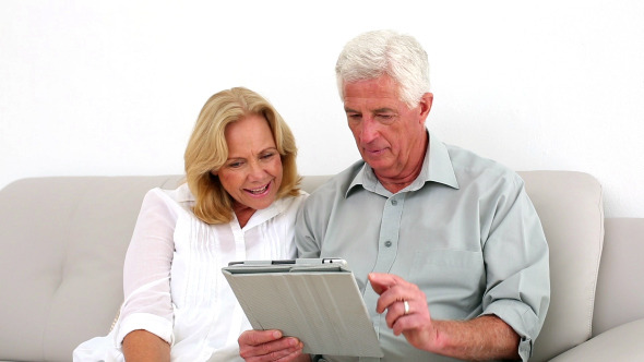 Retired Couple Using Their Tablet On The Couch
