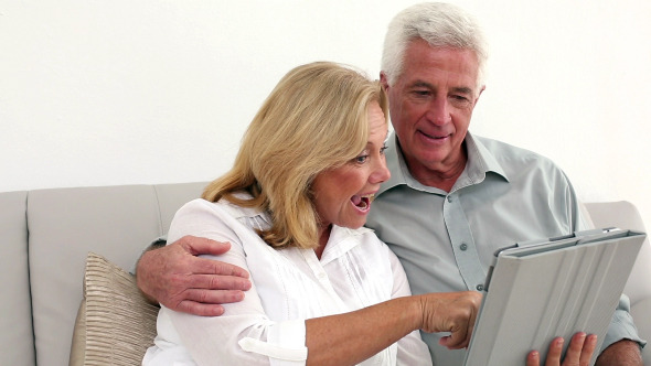 Retired Happy Couple Using Their Tablet