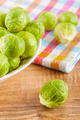 Overhead shot of brussels sprouts in a ceramic bowl and on a wooden table with a cloth rag. - PhotoDune Item for Sale