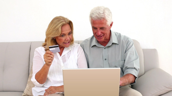 Retired Smiling Couple Using Their Laptop To Shop