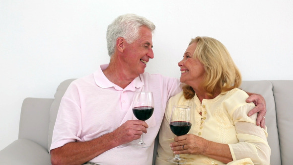 Retired Couple Drinking Red Wine On The Couch