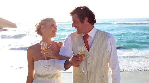Newlyweds Drinking Champagne On The Beach