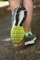 Woman running away from camera close up in trainers
