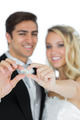 Smiling young married couple holding their wedding rings on white background