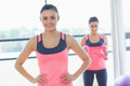 Portrait of a smiling fit young woman with friend in background at a bright exercise room