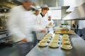 Four chefs working in a modern kitchen preparing soups