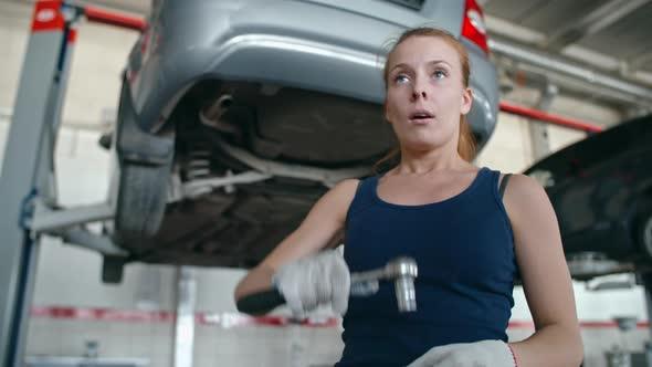 VideoHive Woman Repairing Car Bottom 19662866