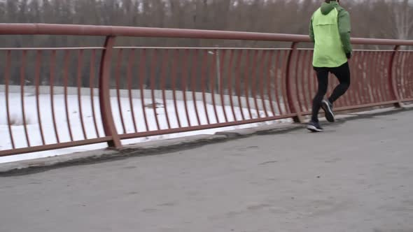Download Man Practicing Winter Running on Bridge nulled download