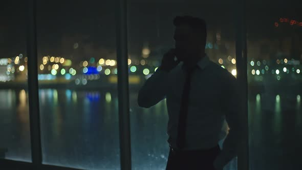 Download Businessman Talking on Phone by Window at Night nulled download