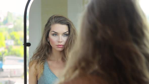 Download Beautiful Woman Looking to the Mirror and Admire Herself nulled download