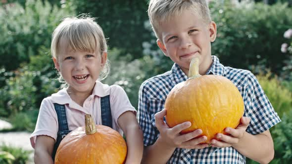 VideoHive Little Boy and Girl Holding Pumpkins 19675477