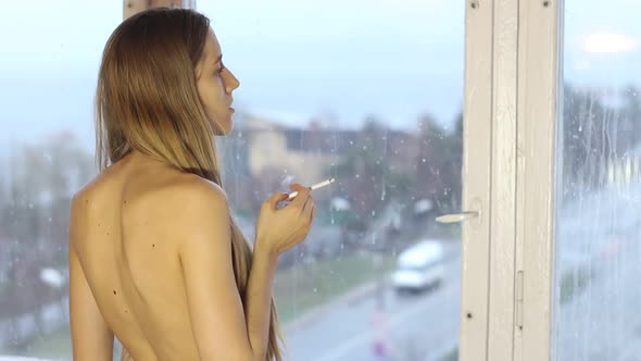 Download Beautiful Sad Girl Smokes By The Window nulled download