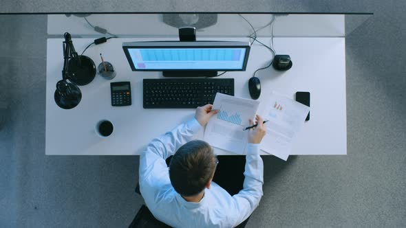VideoHive Top View of an Office Worker Sitting at His Desk Working with Spreadsheets on His Personal Computer 19478707